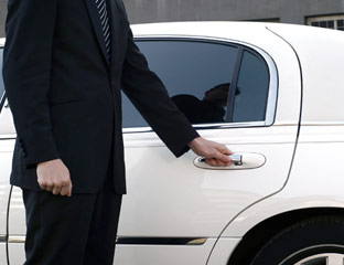 Limo chauffeur hands in envelope stuffed with cash